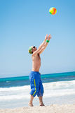Attractive young man playing volleyball on the beach Royalty Free Stock Images