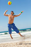 Attractive young man playing volleyball on the beach Royalty Free Stock Photos