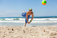 Attractive young man playing volleyball on the beach Royalty Free Stock Photography