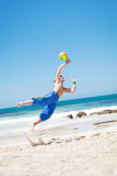 Attractive young man playing volleyball on the beach Stock Images