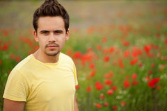 Attractive young man among poppies. Portrait of a young man wearing yellow t-shirt standing in a field of poppies royalty free stock photography