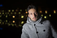 Attractive young man portrait at night with city lights behind him Royalty Free Stock Image