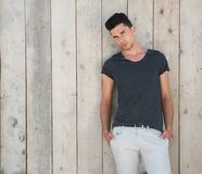Attractive young man posing outdoors against wooden wall Stock Photography