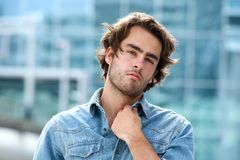 Attractive young man posing outdoors. Close up portrait of an attractive young man posing outdoors royalty free stock images