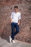 Attractive young man posnig with his hands in pockets. While leaning on a brick wall Stock Photography