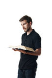 Attractive young man reading a book Stock Image