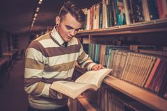 Attractive young man reading a book in the university  library. Royalty Free Stock Photography