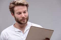 Attractive young man reading on a tablet-pc royalty free stock image