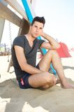 Attractive young man relaxing at the beach in shorts and tshirt Royalty Free Stock Images