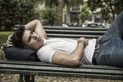 Attractive young man resting on wooden bench Stock Photos