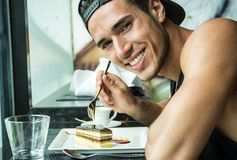 Attractive Young Man`s Breakfast, Eating Cake at Diner stock images