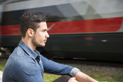 Attractive young man's profile, sitting in front of moving train Royalty Free Stock Photo