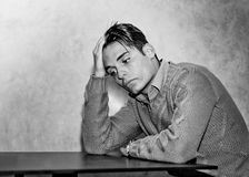 Attractive young man sad or worried. Sad, worried or depressed young man sitting and holding his head Royalty Free Stock Photos