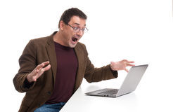 Attractive young man screaming on his laptop Royalty Free Stock Images