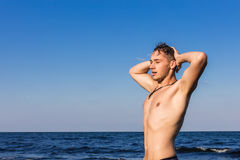 Attractive young man in the sea getting out of water with wet ha Stock Photos