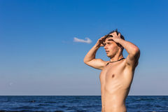 Attractive young man in the sea getting out of water with wet ha. Ir Royalty Free Stock Photo