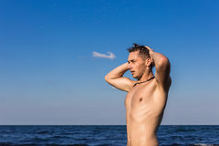 Attractive young man in the sea getting out of water with wet ha. Ir Royalty Free Stock Image