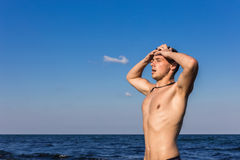 Attractive young man in the sea getting out of water with wet ha. Ir Royalty Free Stock Photography