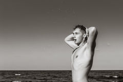 Attractive young man in the sea getting out of water with wet ha. Ir in black and white Royalty Free Stock Image