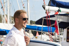 Attractive young man at seaport in front of sailing boat. Stock Photography