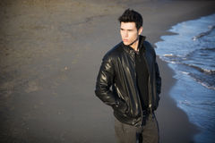 Attractive young man at the seaside on the beach Stock Photos