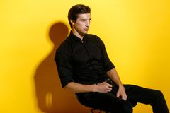 Attractive young man, seated confident on chair, only black wearing, isolated on yellow background. royalty free stock photo