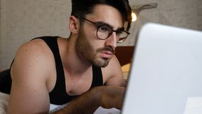Young Man Doing Homework on Laptop in Bedroom Royalty Free Stock Photo