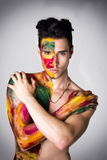 Attractive young man shirtless, skin painted all over with colors Stock Photos