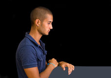 Attractive young man, side view, looking down with hands on board, Royalty Free Stock Image