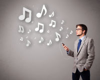 Attractive young man singing and listening to music with musical Royalty Free Stock Images