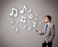 Attractive young man singing and listening to music with musical Royalty Free Stock Image