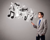 Attractive young man singing and listening to music with musical Stock Images