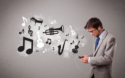 Attractive young man singing and listening to music with musical Royalty Free Stock Photos