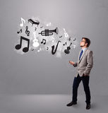 Attractive young man singing and listening to music with musical Stock Photography