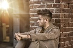 Attractive young man sitting against brick wall Royalty Free Stock Photography