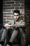 Attractive young man sitting against brick wall Royalty Free Stock Photos