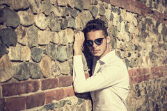 Attractive young man sitting against brick wall Stock Image