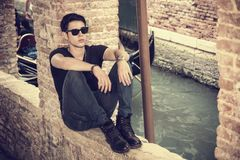 Attractive young man sitting against brick wall Stock Images