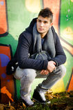 Attractive young man sitting against colorful graffiti Stock Photo
