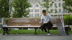 Attractive young man sitting on the bench in the park listening to music on his cellphone then taking crutches and. Skateboard and riding away. Active life of a stock footage