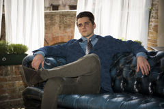 Attractive young man sitting on elegant sofa Stock Image