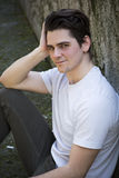 Attractive young man sitting on the ground against rock Stock Photography