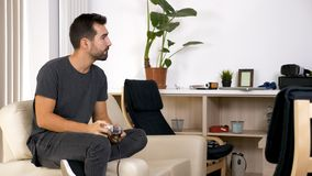 Attractive young man sitting on his couch and playing video games stock photos