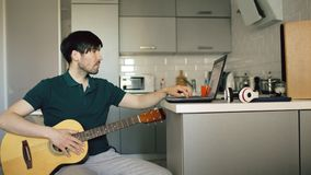 Cheerful young man sitting at kitchen learning to play guitar using laptop computer at home. Attractive young man sitting at the kitchen learning to play guitar Stock Photography