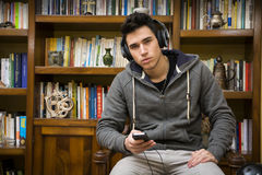 Attractive young man sitting listening to music Royalty Free Stock Image