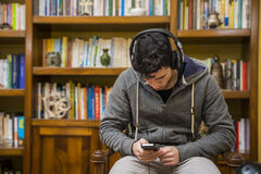 Attractive young man sitting listening to music on a set of stereo headphones Royalty Free Stock Photo