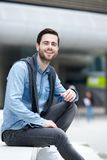 Attractive young man sitting outdoors Royalty Free Stock Photos