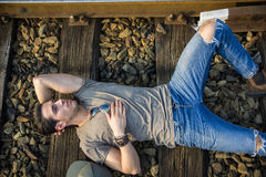 Attractive young man sitting on railroad Royalty Free Stock Images