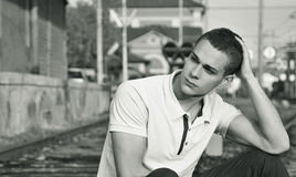 Attractive young man sitting on railroad smiling Stock Images