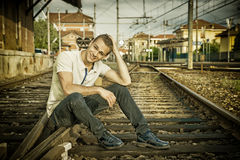Attractive young man sitting on railroad smiling Royalty Free Stock Photography
